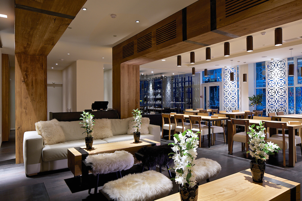Wide-angle view of the dining room from the fireplace space in Georgian restaurant Shoti, Kyiv, Ukraine. Modern european design mixes with traditional georgian decorative elements and materials. Wooden frames surround seating next to the fireplace.