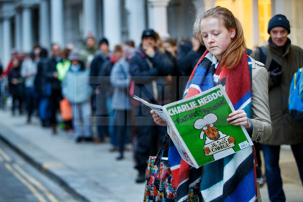 © Licensed to London News Pictures. 16/01/2015. LONDON, UK. Elli Watson reading a copy of Charlie Hebdo's survival edition after buying it from 'The French Bookshop' in London on Friday, 16 January 2015. Photo credit : Tolga Akmen/LNP