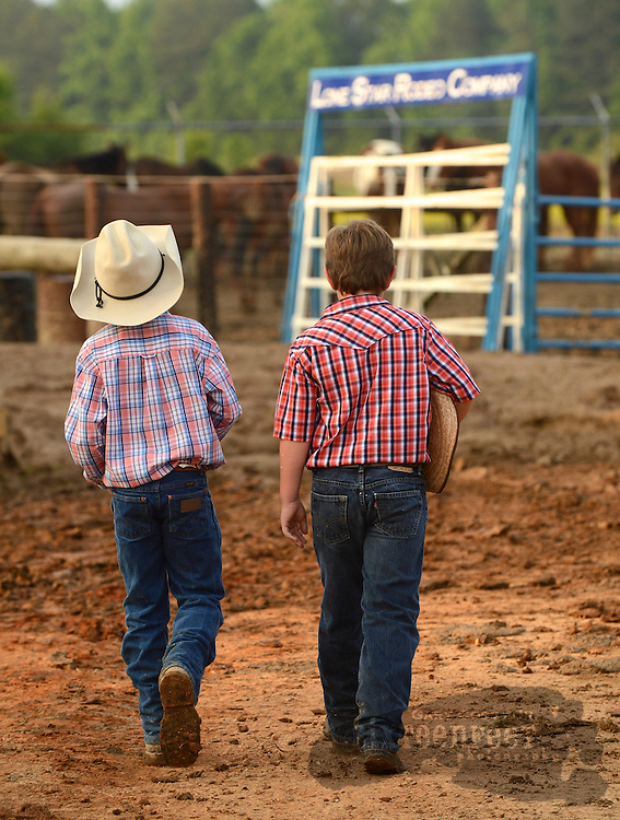Photo by Gary Cosby Jr.    Noah Moran and Ethan Keeton walk together near the cattle holding pens before a Sunday evening makeup at the Limestone Sheriff's Rodeo in Athens.  An earlier performance was rescheduled due to the severe weather Friday.