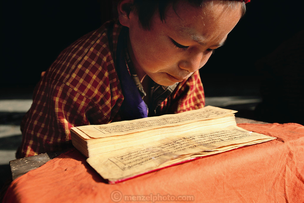 A young Buddhist monk reads holy scripts aloud at the Gangte Goemba (monastery) in Phobjikha Valley, Bhutan. The monastery dates back to the 1600's and includes one of the largest prayer halls in the country and a meditation center for monks. The government financed the building of a Buddhist college here in the 1980's.