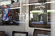 window reflection with images of young woman in kimono Display of local photo portrait studio in Japan