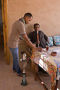 A local man is served chai (tea) and enjoys a shisha in the village of Medinet Habu on the West Bank of Luxor, Nile Valley, Egypt.