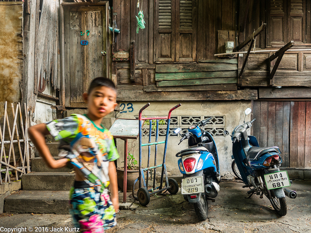 07 APRIL 2016 - BANGKOK, THAILAND: A child walks past a 200 year old home in Mahakan Fort. The home, one of the original homes in the squatters' community in the fort, was built without nails using a wedging technique. The concrete base was added a few years ago. Mahakan Fort was built in 1783 during the reign of Siamese King Rama I. It was one of 14 fortresses designed to protect Bangkok from foreign invaders, and only of two remaining, the others have been torn down. A community developed in the fort when people started building houses and moving into it during the reign of King Rama V (1868-1910). The land was expropriated by Bangkok city government in 1992, but the people living in the fort refused to move. In 2004 courts ruled against the residents and said the city could take the land. The final eviction notices were posted last week and the residents given until April 30 to move out. After that their homes, some of which are nearly 200 years old, will be destroyed.       PHOTO BY JACK KURTZ