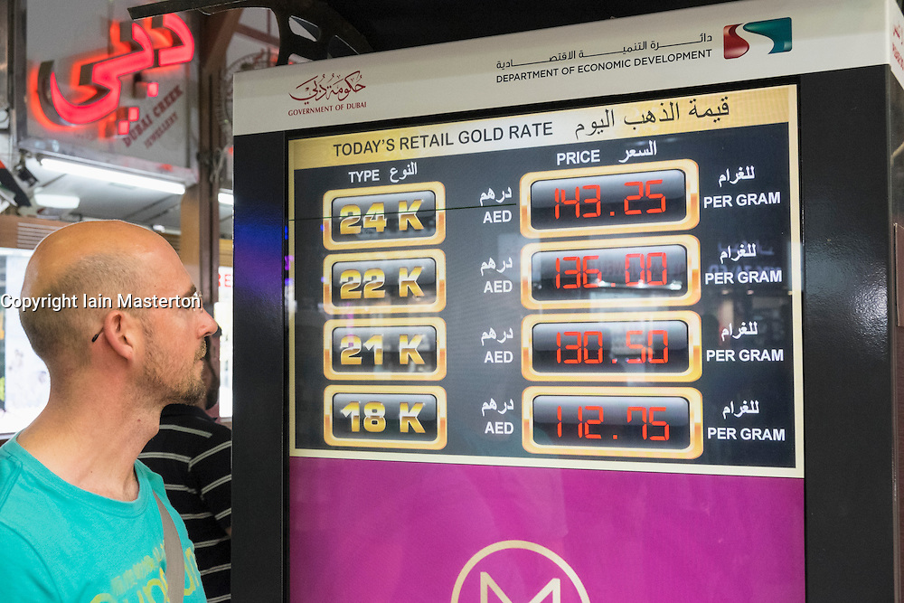 Tourist looking at current price of gold on electronic display at the Gold Souk in Deira Dubai United Arab Emirates