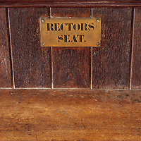 Antique brass plate screwed to front of backrest of wooden church pew stating Rectors seat