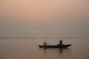 Boat with tourist photographing sunrise over the Ganges river at Varanasi (India)