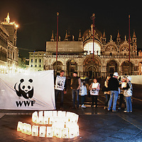 VENICE, ITALY - MARCH 31: Members  of WWF stands in front of lanterns creating a 60 in St Mark's Square while lights are switched off for Earth Hour 2012 on March 31, 2012 in Venice, Italy. According to organizers, Earth Hour 2012 has participants including individuals, companies and landmarks in 147 countries and territories and over 5,000 cities agreeing to switch off their lights for one hour. The Brandenburg Gate, the Eiffel Tower in Paris, Big Ben Clock Tower in London, the Christ the Redeemer statue in Rio de Janeiro and the Empire State Building in New York are among the monuments whose operators have agreed to participate in the demonstration.  (Photo by Marco Secchi/Getty Images)