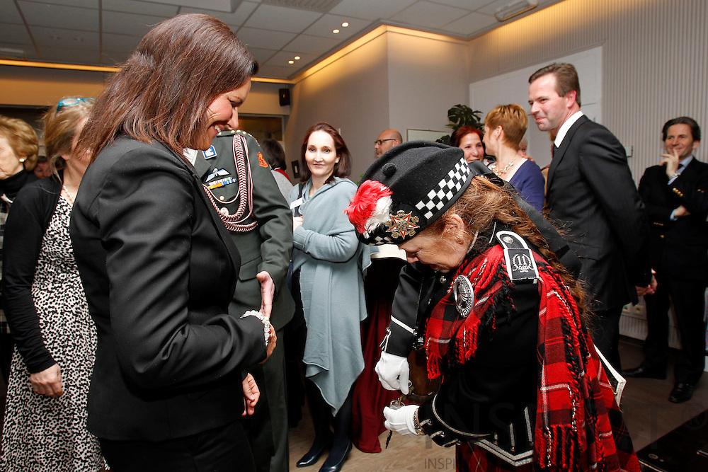BRUSSELS - BELGIUM - 11 MARCH 2010 --  Anne-Mette Rasmussen dansede sig til 10.000 euro i december 2009 sammen med hendes dansepartner fra TV-showet Vild med Dans, Thomas Evers Poulsen, i et velgørenhedsarrangement i Nato's hovedkvarter i Bruxelles..Pengene blev uddelt i 2 portioner a 5000 euro og til to forskellige organisationer som arbejder med bedre uddannelse for kvinder og børn i Afghanistan. Overrækkelsen fandt sted i de samme lokaler som velgørenhedsarrangementet i december..Den ene check blev modtaget af den afghanske ambassadørfrue Seema Nezam's organisation Afghan Women Advancement, som hun er president for. De andre 5000 euro gik til Afghan Appeal Fund og blev modtaget af presidenten for Nato's internationale klub Conny Godderij og bestyrelsesmedlem Hilary Thorn..Pengene vil gå ubeskåret til skoler og uddannelse i Afghanistan..Anne-Mette Rasmussen kunne efter overrækkelsen meddele at hun vil gentage succesen igen den 4 juni ved endnu en velgørenhedsmiddag. Der havde været mange positive tilbagemeldinger fra deltagerne. De synes om ideen at forene velgørenhed og socialt samvær..Begivenheden fandt sted i forbindelse med festligholdelsen af Nato's Internationale Klubs 40 års jubilæum, som er en klub for ansatte i NATO og EU's institutioner i Bruxelles..Anne-Mette's ægtefælle, Nato's generalsekretær Anders Fogh Rasmussen, var forhindret i at deltage, da han var på vej til Polen på officielt besøg..Her får hun et glas Jenever serveret af kvinde klædt i skotsk kostume direkte fra et lille træanker. PHOTO: ERIK LUNTANG / INSPIRIT Photo