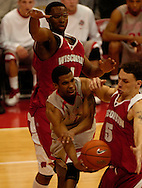 MORNING JOURNAL/DAVID RICHARD.Mike Conley Jr., center, of Ohio State dishes off while defended by Marcus Landry, back, and Jason Chappell of Wisconsin Sunday, Feb. 25, 2007, in Columbus, Ohio. Ohio State beat Wisconsin 49-48.