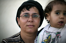 "Aliza Cohen, 40, a teacher who has lived in the Gush Katif settlements for 20 years, is seen in Gaza, Palestinian Territories, Nov. 4, 2004. When asked her thoughts about leaving the settlements, Cohen responded, ""My husband was moved from Egypt and now we are being asked to move again. It's very hard. We have built a beautiful place out of nothing. We built a family and life here. I pray that God will help us."" Israel's parliament recently supported compensation payments for Jewish settlers leaving the Gaza Strip, in a vital vote for Prime Minister Ariel Sharon's plan to evacuate the occupied territory."