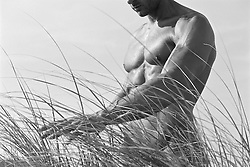 nude man walking in tall beach grass