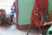 1/5/01 -- (PHOTO BY MIKE FENDER) w/ story, slug: AFRICA, file: 62040 // Children living at a home in Addis Ababa run by a monk watch as Cheryl Carter-Shotts visits with Tarekwa and looks at her leg during a visit in January. The girl was later moved to the Americans for African Adoption foster home and has an adoption in the works that will send her to Boston.