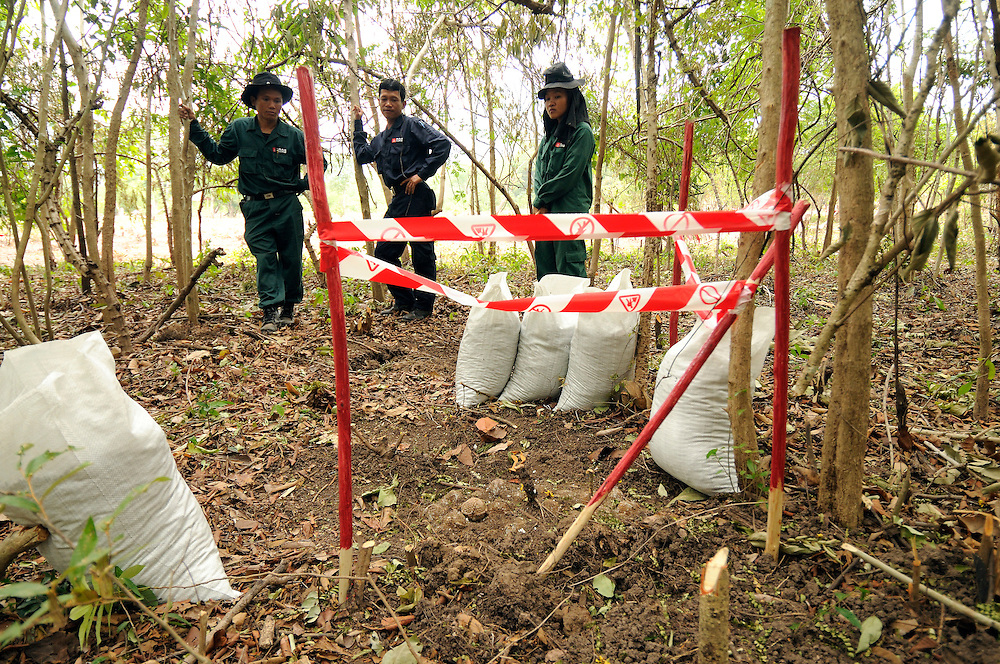 """Somma Phalangsy, age 33 (left), Phet Senthavisouk (center), and Phisamai Linsaiyoum, age 20 (right), look at a pile of 20, BLU 26 cluster bombs, laying buried in the dirt after being located by one of the Mines Advisory Group ladies teams.  Cluster bombs like these are extremely dangerous and can explode with the slightest movement.  When detonated each bomb has hundreds of metal pellets that fire out at ballistic speed.  Female Deputy Team Leader, Phisamai Linsaiyoum, age 20 (right) disposed of the bombs without moving them in a controled demolition using TNT and C4 explosives...Laos was part of a """"Secret War"""", waged within its borders primarily by the USA and North Vietnam.  Many left over weapons supplied by China and Russia continue to kill.  However, between 90 and 270 million fist size cluster bombs were dropped on Laos by the USA, with a failure rate up to 30%.  Millions of live cluster bombs still contaminate large areas of Laos causing death and injury.  The US Military dropped approximately 2 million tons of bombs on Laos making it, per capita, the most heavily bombed country in the world. ..The women of Mines Advisory Group (MAG) work everyday under dangerous conditions removing unexploded ordinance (UXO) from fields and villages...***All photographs of MAG's work must include (either on the photo or right next to it) the credit as follows:  Mine clearance by MAG (Reg. charity)***."""