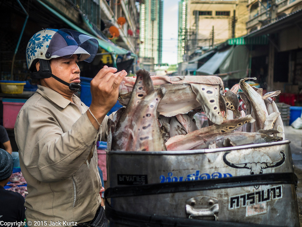 14 AUGUST 2015 - BANGKOK, THAILAND:  A worker loads frozen fish onto his motorcycle in an alley next to Saphan Pla fish market in Bangkok. He was delivering the fish to a customer. Saphan Pla fish market is the wholesale fish market that serves Bangkok. Most of the fish sold in Saphan Pla is farmed raised fresh water fish. The market is open 24 hours but it's busiest in the middle of the night and then again from about 7.30 until 11 in the morning.       PHOTO BY JACK KURTZ