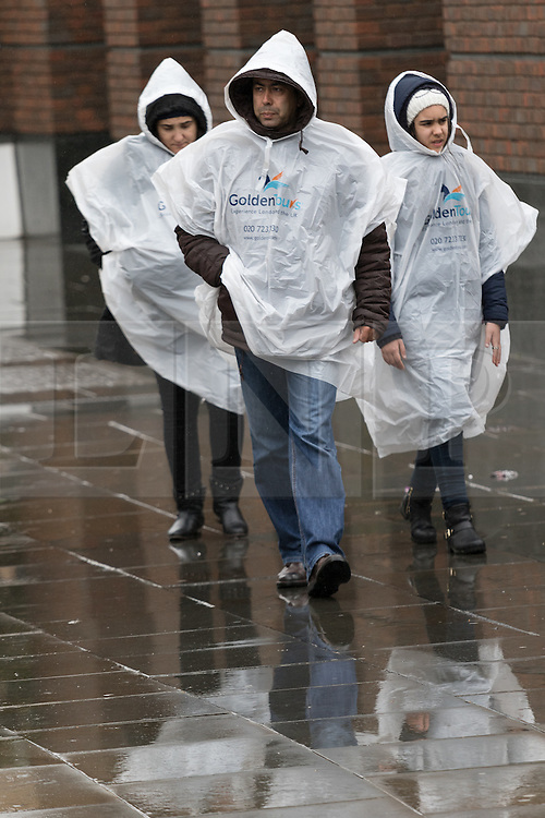 © Licensed to London News Pictures. 29/05/2015. London, UK. Tourists walk in rain ponchos near St Paul's Cathedral during wet and overcast weather in London. Today is the first day of British Summer Time (BST). Photo credit : Vickie Flores/LNP