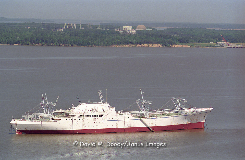 "Nuclear powered cargo ship SS Savannah mothballed with the ""ghost fleet"" on the James River in Virginia. The Surry nuclear power plant is on shore directly behind the ship."