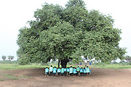 Children attend primary school under a tree near Terakeka, South Sudan. Years of conflict dispersed communities and decimated infrastructure. As South Sudan attempts to build itself, open air schools are popping up until school houses can be built.