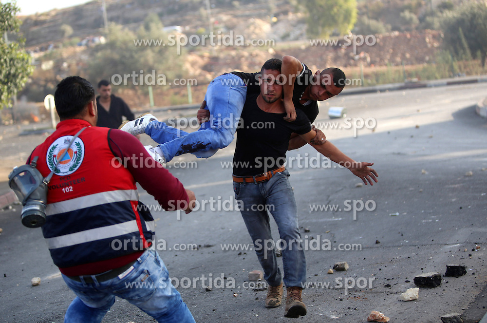 08.10.2015, Ramallah, PSE, Gewalt zwischen Pal&auml;stinensern und Israelis, im Bild Zusammenst&ouml;sse zwischen Pal&auml;stinensischen Demonstranten und Israelischen Sicherheitskr&auml;fte // A Palestinian protester carries his wounded fellow during clashes with Israeli security forces in Beit El, near the West Bank city of Ramallah. New violence rocked Israel and the Israeli occupied West Bank, including an incident in which men thought to be undercover Israeli police opened fire on Palestinian stone throwers they had infiltrated, wounding three of them, Palestine on 2015/10/08. EXPA Pictures &copy; 2015, PhotoCredit: EXPA/ APAimages/ Shadi Hatem<br /> <br /> *****ATTENTION - for AUT, GER, SUI, ITA, POL, CRO, SRB only*****