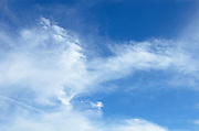 Blue sky with white cirrus and stratus clouds.