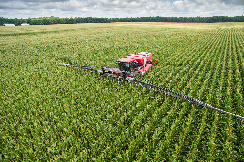 An aerial view of an air seeder working its way through rows and fields of cover crops, turning these crops into corn.
