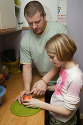 Single parent helping young daughter slice an apple in the kitchen,
