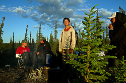"""Brendan Felix Head, 14, relaxes after cutting wood for a campsite as First Nation Dene youth finish their trip from the Upper Thelon River, where their ancestors believe is """"the place where God began.""""  Sparsely populated, today few make it into the Thelon. Distances are simply too far, modern vehicles too expensive and unreliable. For the Dene youth, faced with the pressures of a western world, the ties that bind the people and their way of life to the land are even more tenuous. Every impending mine, road, and dam construction threatens to sever these connections. In July and August, 2011 a group of youth paddled to their ancestral hunting ground and spiritual abode.  this next generation of young leaders will be the ones who will need to speak for the Thelon the loudest. (Photo by Ami Vitale)"""