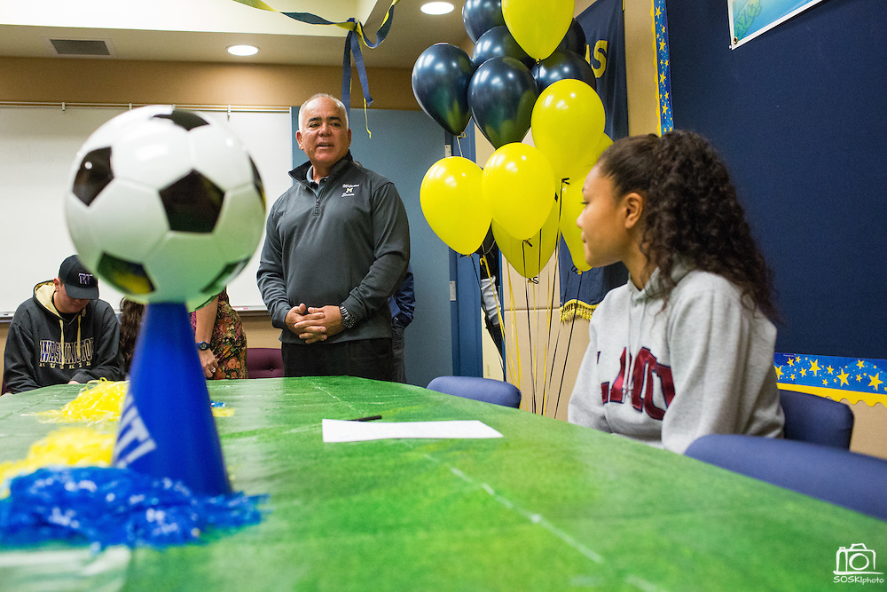 Milpitas High School Soccer coach Michael Tomlin (left) shares memories about Sarina Bolden (right) with guests before Bolden signs a duplicate National Letter of Intent to play soccer at the Loyola Marymount University during the NCAA National Signing Day event at Milpitas High School in Milpitas, California, on February 4, 2015. (Stan Olszewski/SOSKIphoto)