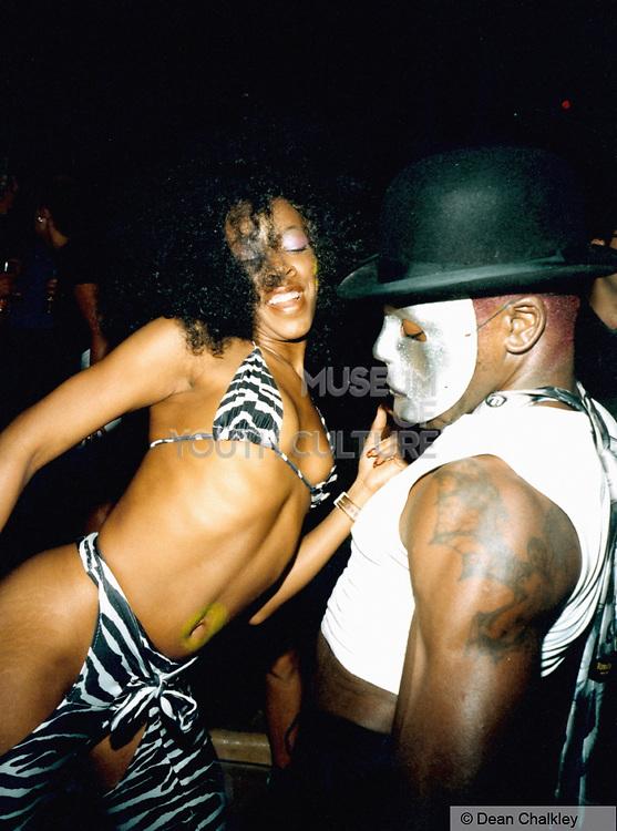 Woman wearing a zebra print bikini, man wearing a silver mask, Ibiza 1999