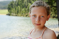 Girl (7-9) standing by lake portrait.