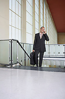 Business man using mobile phone in airport lobby on stairs