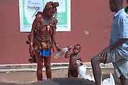 "A traditionally dressed Himba woman with her child outside a supermarket in Opuwo, a town well known for cultural tourism in northwestern Namibia, after receiving money from a tourist in exchange for a photograph.  Like most traditional Himba women, she covers herself from head to toe with an ochre powder and cow butter blend. Some Himba are turning to tourism to kick-start their entry into the cash economy, setting up demonstration villages advertising ""The Real Himba."""