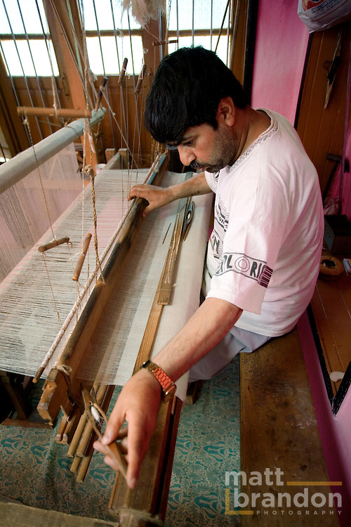 A weaver begins to send the shuttle through pashmina threads as he weaves a shawl on a hand loom in Kashmir.