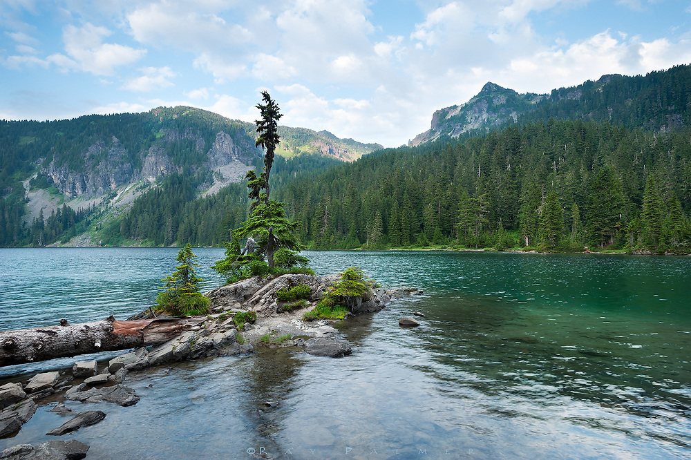 Mowich Lake, Mount Rainier, Washington.   <br /> Wind and water. That is the literal translation of the Chinese science of Feng shui, which seeks to bind humanity with it&rsquo;s surroundings.  The idea incorporates positive and negative polarity (yin and yang) as well as the five elements (wood, water, fire, metal and earth).  The practice channels the energy, the life force of a place, known as Qi (pronounced chee), to place architecture in the most auspicious direction and orientation.  In a sense it is an alignment between what you build and how you live with the universe, positioning your structure with water, land forms, even compass points and constellations. My more immediate universe changes daily though, and tonight I am here in a glacial bowl on the northwest flank of Rainier.  Rainier is huge, easily seen 70 miles away in Seattle.  It is so massive that weather gets backed up in its directional flow, accounting for many of the moods of the mountain, from serene and welcoming to angry and deadly.   I am not the architect whose hand made the little bump of land before me;  this is Rainier&rsquo;s feng shui.  Maybe it&rsquo;s a push of magma, or one piece of puzzle from continental uplift millennia ago, but it was the hand of the mountain itself that placed this little island, and you can still feel the Qi.  It is one of countless perfect designs of this place, if your eyes are open to them.  This one is aligned eastward, spring-like and appropriate to Rainier&rsquo;s green season, and pointing to the constellation of Scorpius, coincidentally my astrological sign.   There are times I have to escape every day life, with all it&rsquo;s yin and yang, letting my thoughts either breathe or rest.  If I wasn&rsquo;t looking for harmony, I have found it anyways, and tonight, I will sit and contemplate the wind and water.