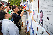 03 MARCH 2013 - BANGKOK, THAILAND: <br />  People check the names on voter lists at a polling place in Benchasiri Park in Bangkok. Bangkok residents went to the polls Sunday to elect a new governor. Voter turnout was expected to be heavy for a local election. Pongsapat Pongchareon, the Pheu Thai candidate is thought to hold a slight lead over Sukhumbhand Paribatra, the Democrats' candidate. There are a total of 25 candidates in the election but only Pheu Thai and the Democrats are given a chance of winning.    PHOTO BY JACK KURTZ