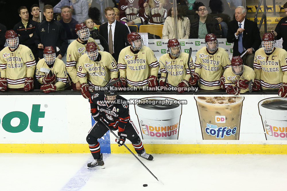 Adam Reid #8 of the Northeastern Huskies controls the puck in front of the Boston College bench during The Beanpot Championship Game at TD Garden on February 10, 2014 in Boston, Massachusetts. (Photo by Elan Kawesch)