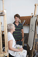 Artist drawing portrait in studio young man looking on