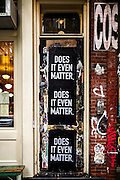 "A doorfront in New York City's East Village with sticks containing the phrase ""Does It Even Matter"""