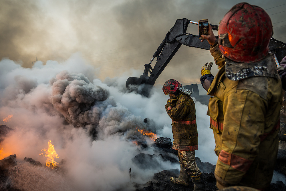 Firefighters stand on the edge of a blazing oil pit as they work to extinguish the flames in the Qayyarah oil field on December 12, 2016. Despite the intensity of the flames one of the firefighters takes a moment to take a selfie with his phone. <br />