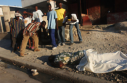 A group of people eye the body of a woman who had been shot.   It is often difficult to transport the dead or wounded to area hospitals as Red Cross ambulances refuse to enter some neighborhoods and family members are afraid that any gun shot victim will be taken from the hospital and put in jail. The security situation in Haiti has deteriorated in recent months with many Hatians and human rights groups accusing the Haitian National Police and various gangs of human rights violations.