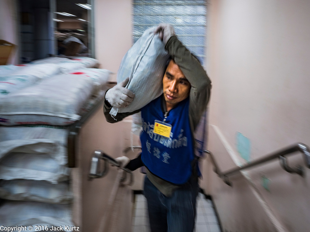 30 AUGUST 2016 - BANGKOK, THAILAND: A volunteer with Poh Teck Tung carries a sack of rice into a food distribution at the shrine on the last day of Hungry Ghost Month in Bangkok. Chinese temples and shrines in the Thai capital host food distribution events during Hungry Ghost Month, during the 7th lunar month, which is usually August in the Gregorian calendar.         PHOTO BY JACK KURTZ