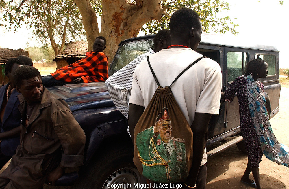 Holding a back bag with the image of Sudan's president Omar Al-Bashir, Kutey, a young man, waits for a transportation in the town of Ayod, days after the celebration of the Referendum for independence in South Sudan. (PHOTO: MIGUEL JUAREZ LUGO).