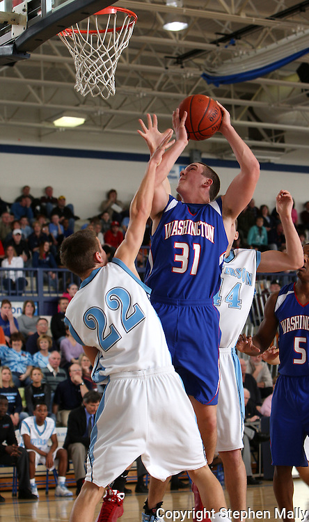 Washington's Wyatt Suess is fouled by Jefferson's Joby Frey (22) as he tries to shoot a basket during the first half of their game at Jefferson High School in Cedar Rapids on Friday February 6, 2009. Washington led 33-14 at halftime.