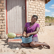 CAPTION: Sibongile prepares maize (corn) outside her home. During recent droughts, maize - one of the staples of the region - has been amongst the hardest hit crops. The Bindagombe Irrigation Scheme will help to preserve these crops during times of drought. LOCATION: Mawoneke Village, Chivi District, Masvingo Province, Zimbabwe. INDIVIDUAL(S) PHOTOGRAPHED: Sibongile Mawoneke.
