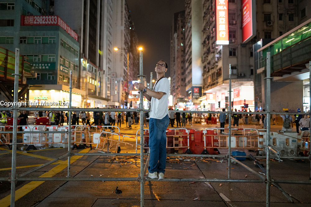 Hong Kong, China. 13th October 2019. Woman suspected of being pro-Beijing is assaulted by pro-democracy protestors in Mongkok district in Kowloon on Sunday evening. This incident was one of several throughout Hong Kong on Sunday which saw acts of vandalism carried out by a minority in the pro-democracy movement. Man stands on barricade on Nathan Road. Iain Masterton/Alamy Live News.