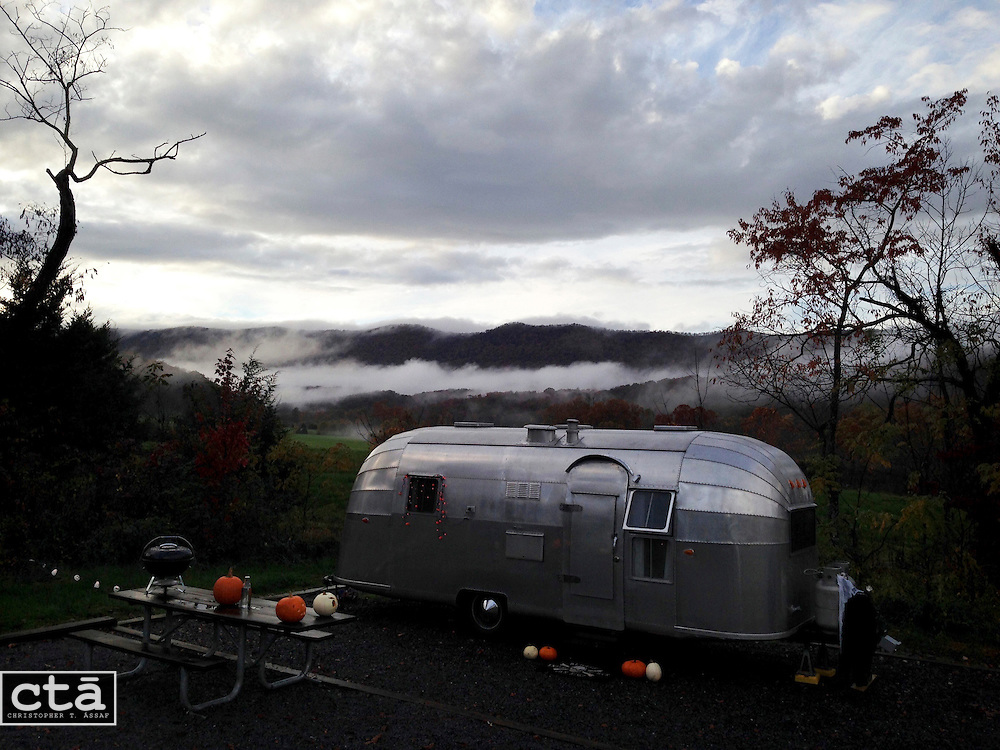 A fast moving storm has just passed, and a vintage Airstream sits on wet ground as the sun sets at Shenandoah River State Park on Halloween weekend.