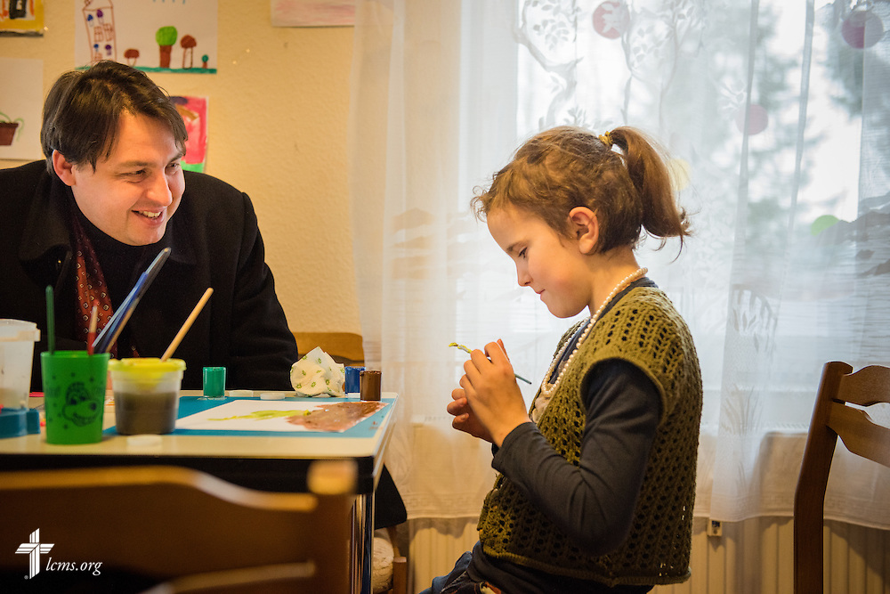 The Rev. Mindaugas Kairys joins a young girl as she paints at the Diaconia daycare center under the Evangelical Lutheran Church in Lithuania on Friday, Feb. 6, 2015, in rural Skirsnemune, Lithuania. LCMS Communications/Erik M. Lunsford