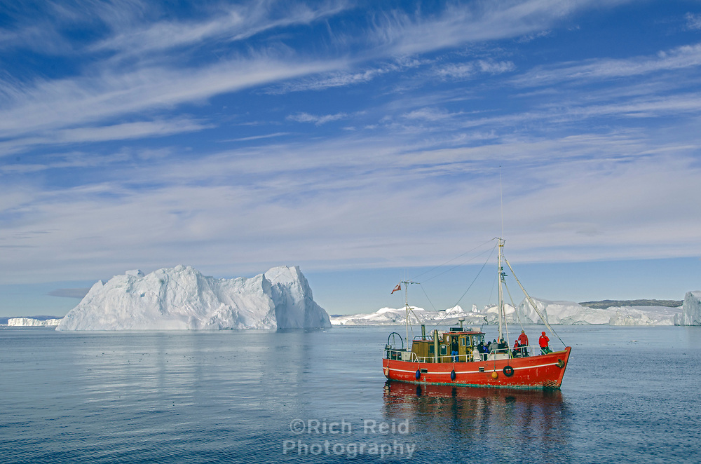 Red boat in the glacial Ice in Ilulissat Icefjord from Jakobshavn Glacier or Sermeq Kujalleq near Ilulissat, Greenland. The Jakobshavn is one of the fastest moving glaciers in the world and a UNESCO World Heritage Site.