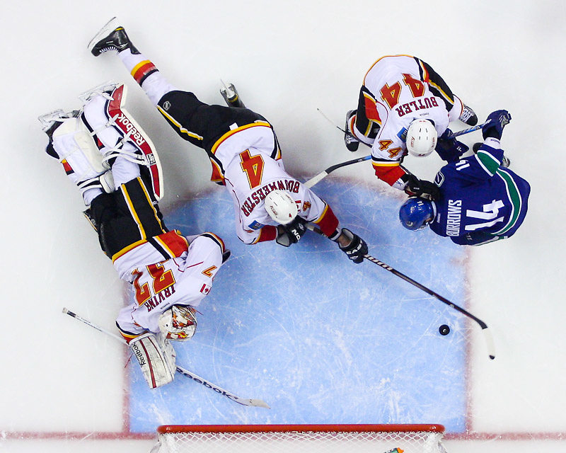 VANCOUVER, CANADA - DECEMBER 23: Chris Butler #44 of the Calgary Flames stops Alexandre Burrows #14 of the Vancouver Canucks before he can get to the loose puck in front of the crease in NHL action on December 23, 2011 at Rogers Arena in Vancouver, British Columbia, Canada. (Photo by Derek Leung/Getty Images)