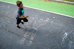 A boy runs past a chalk drawing of Rocky as community members celebrate summer at the Oval, on the Benjamin Franklin Parkway, in Philadelphia, PA on July 20, 2018. A pop-up public space featuring play, and spray-ground, beer garden, food trucks and entertainment is installed at Eakins Oval near the Art Museum steps till August 19th.