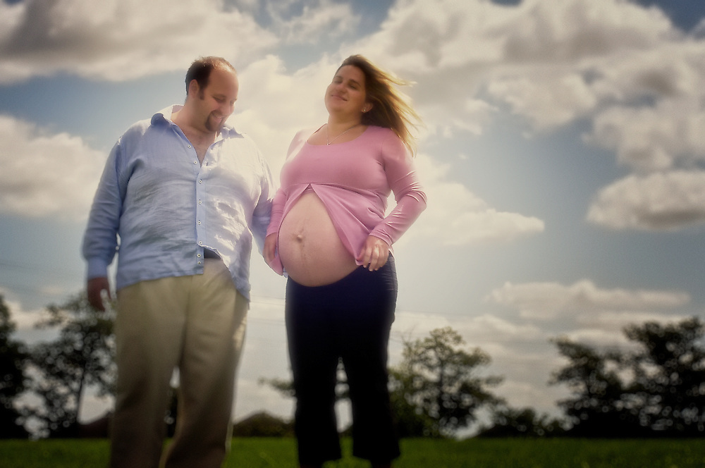 A father-to-be walks with his expecting wife, her tummy exposed, on a cloudy spring day